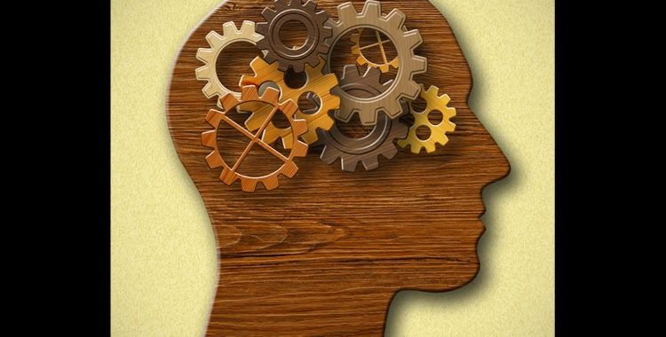 Wooden silhouette of head with brown-tone gears running inside where brain would be