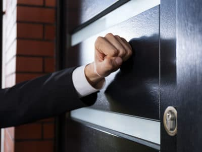 arm of person wearing a suit knocking on the door to someone's home