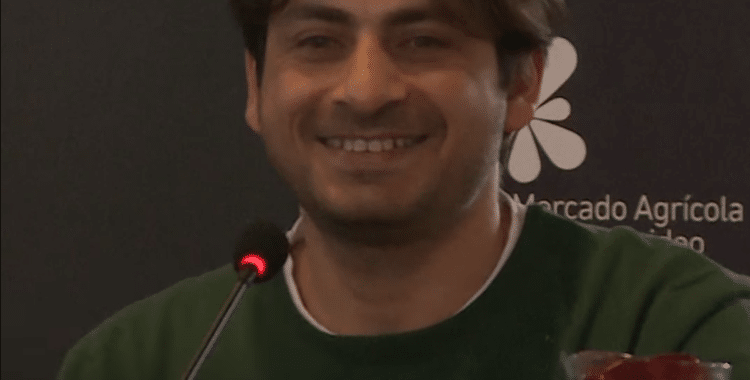 Ahmed Ajam wearing a green shirt speaking into a microphone