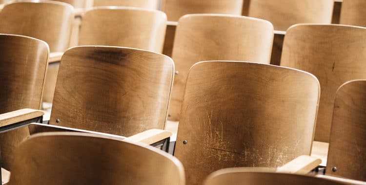 rows of wooden seats in an auditorium