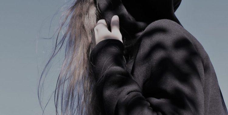 Young girl in black hoodie pulling hood over her head