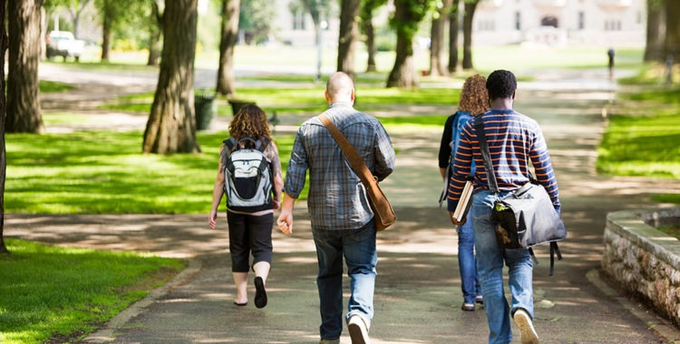 Rear view of university students with backpacks walking on campus road