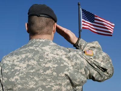 back view of soldier in camouflage uniform saluting American flag