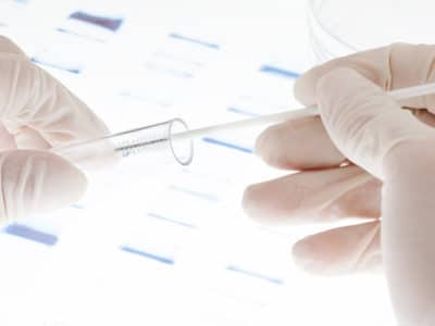 Researcher putting sample of DNA test into a test tube