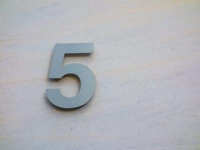 steel number five on a light beige marble wall