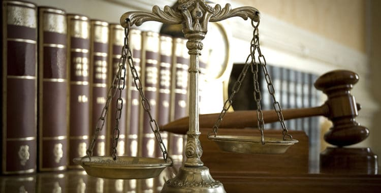 Scales of Justice and Judge's gavel with rows of books in background
