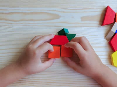 child playing with colored blocks constructing a model on a light wood table