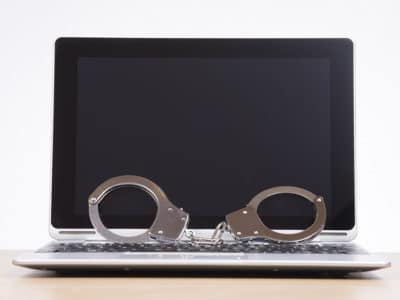 Pair of handcuffs resting on the keyboard against a blank laptop screen