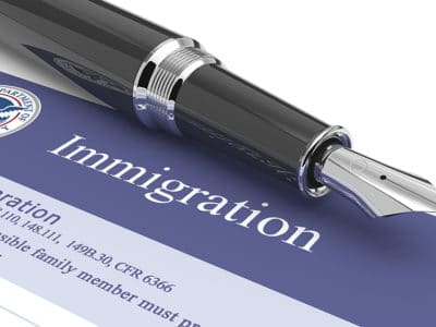 Black pen sitting atop immigration form