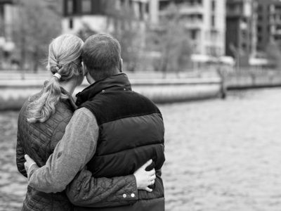 grayscale photo of the backs of a young couple wrapping their arms around each other and looking at a river