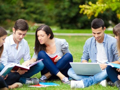 Group of college students sitting on grass in the park doing homework
