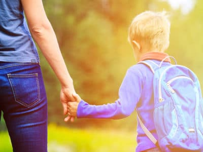 Mother holding hand of young son wearing backpack outdoors