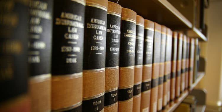 Close up of volumes of law books sitting on a shelf in a library