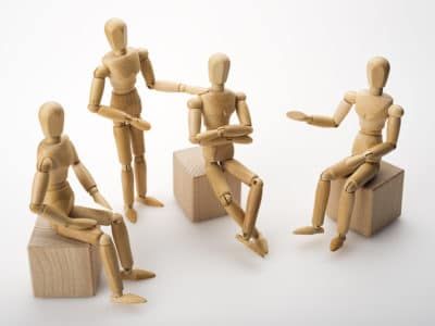 wooden dolls posed for group therapy session
