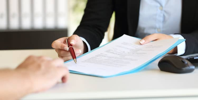 Close up of a professional's hands holding a pen and indicating where to sign a contract at office