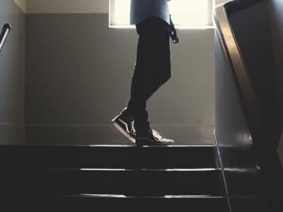 teenage boy turning corner of high school hallway stairs