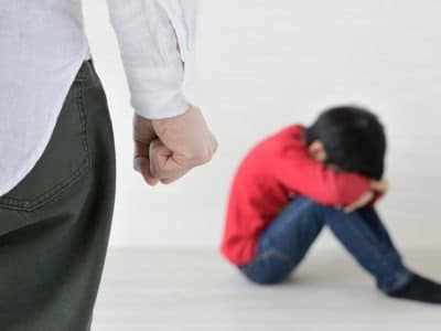 clenched fist of adult with blurry child sitting with head down in background