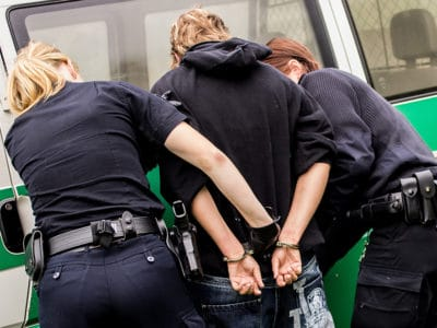 Female police officers arresting young man in front of white and green vehicle