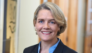 Head shot of Kristina Selset wearing navy blue suit in The Marshall Defense Firm office