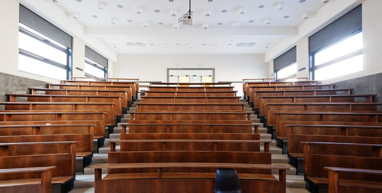 Empty classroom with one black chair in front